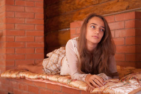 Girl warming on the  stove in old wooden house photo