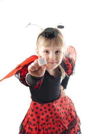 Girl in ladybug costume on white background showing white cube photo