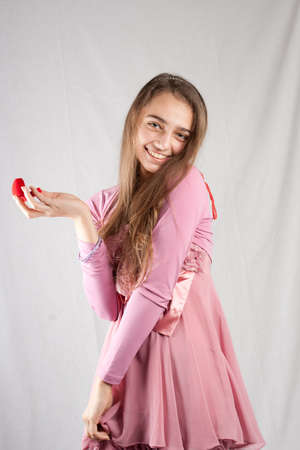 Teenage girl in pink holding plush heart photo