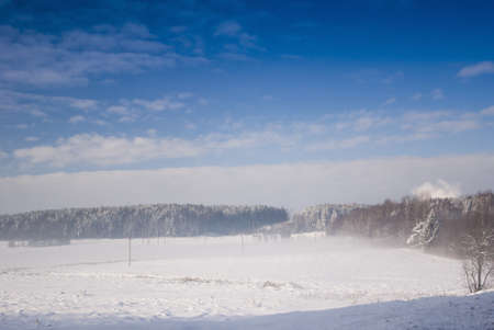 winter meadow landscape with blue cky and clouds photo