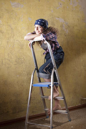 girl standing on the ladder in jeans Stock Photo - 12394413