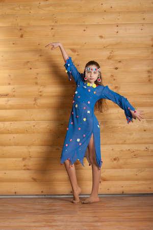 ethnic dress: Danza Ragazza in abito blu etnico vicino al muro di legno Archivio Fotografico
