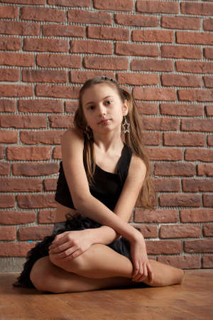 Girl in black skirt and top sitting near brick wall