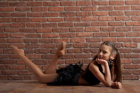 Girl in black skirt lying near brick wall photo