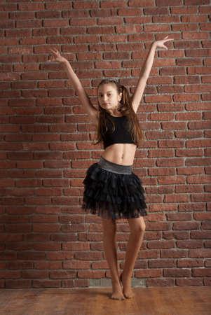 Girl in black skirt  dancing near brick wall