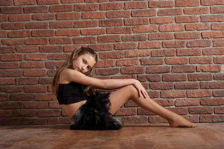 Girl in black dancing skirt   sitting near brick wall