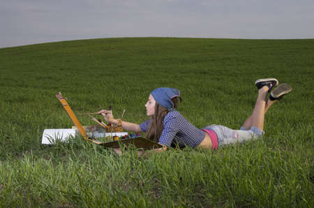 Girl painting landscape on the meadow outdoor in evening