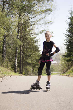 Young girl  skating on Roller Skates outdoor at trail photo