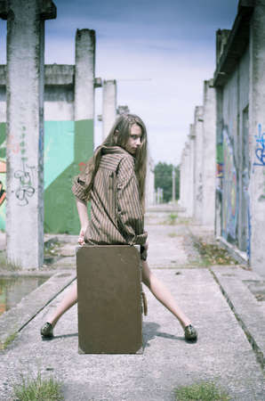 Girl in mens shirt sitting on the suitcase in unconstructed building photo