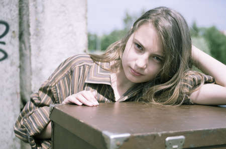 Girl in mens shirt near suitcase in unconstructed building photo