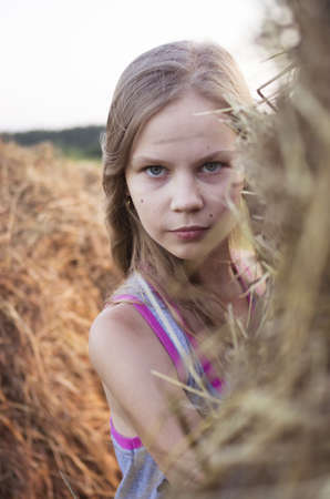 Portrait of teenage girl in the field with corn ears and straw Stock Photo - 14904234