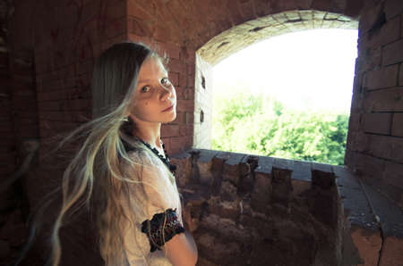 Portrait of teenage girl staying near window hole in  brick wall inside ruins Stock Photo