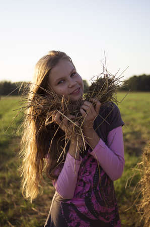 Portrait of teenage girl in the field with corn ears and straw photo