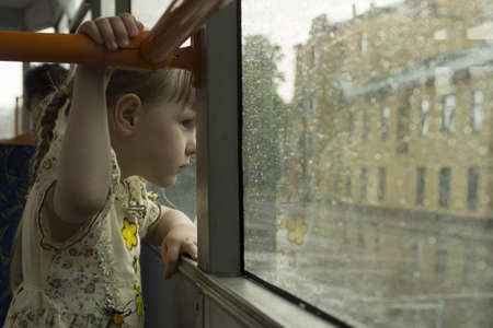 Little girl looking throw tram window at the rain photo