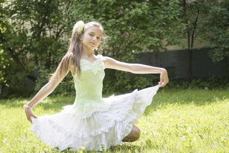 teenage girl sitting in light dress on the grass Stock Photo - 15335985