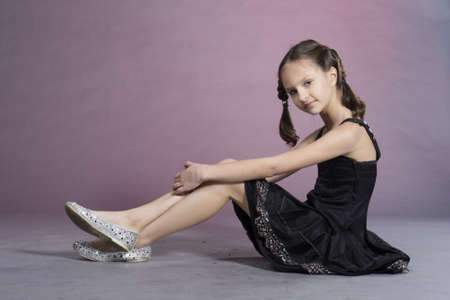 Little preteen nice smiling girl posing in studio