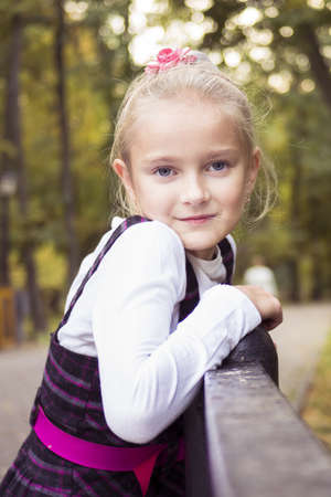 Little preteen girl standing near railing in park at autumn photo