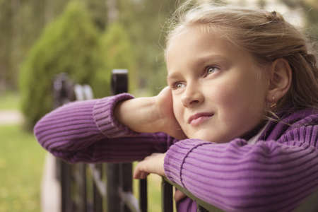 beautiful blonde girl with green eyes: Little preteen girl staring into infionity outdoor in park at autumn
