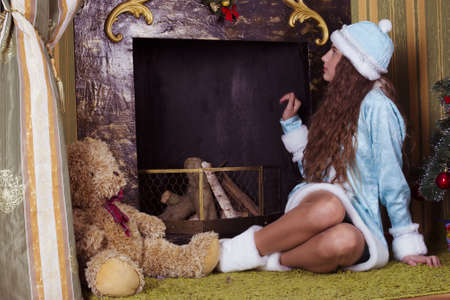 teen girl in Snow-maiden  costume looking into fireplace chimney photo