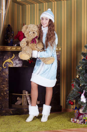 teen girl in Snow-maiden  costume holding teddy bear near  fireplace photo