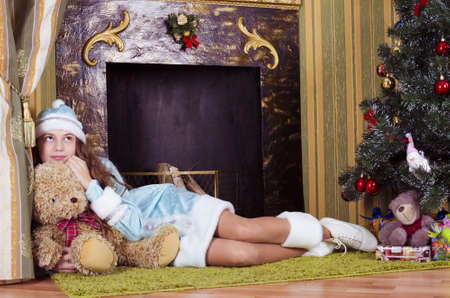 nice teen girl in Snow-maiden  costume lying near fireplace with teddy bear photo