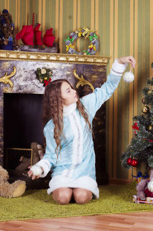 nice teen girl in Snow-maiden costume looking at Christmas balls photo