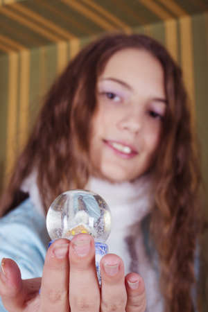 nice teen girl in Snow-maiden costume showing snow globe photo
