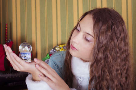 nice teen girl in Snow-maiden costume looking at  snow globe photo