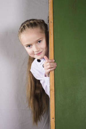 nice schoolgirl peeking out from school board in studio photo