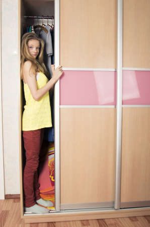 teenage girl hiding in wardrobe at home Stock Photo