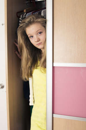 teenage girl peeking out from wardrobe at home photo