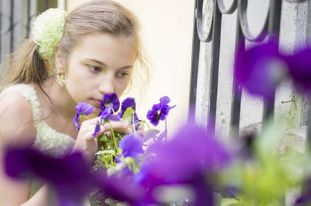 window grill: young girl sniffing beautifull blue flowers near window grill