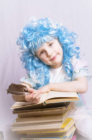 little girl with blue hair and quill pen sitting near stack of books photo
