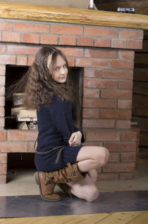 young girl in blue jersey heating near red brick fireplace photo