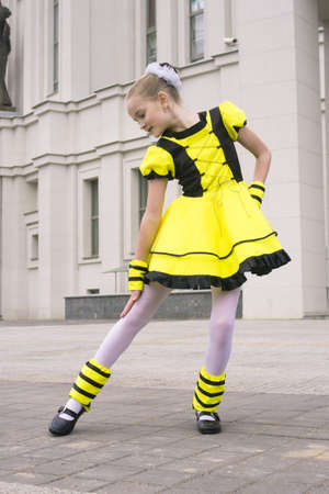 little girl dancing outdoor in bee costume near the building photo