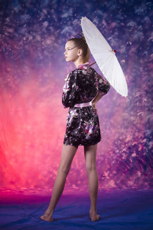 young teenage girl looking to the side in floral kimono in studio photo