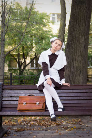 nice young teenage schoolgirl sitting on the bench in the park photo