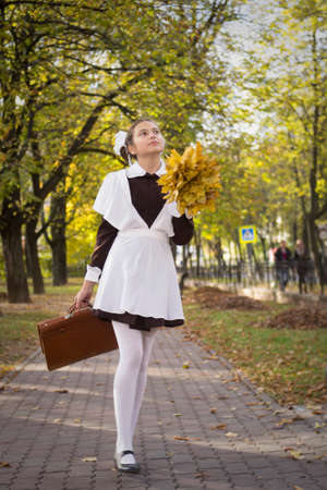 nice young teenage schoolgirl with autumn leaves in the park