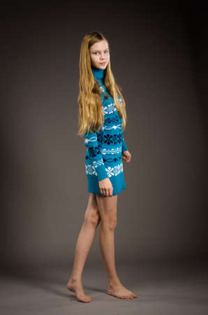 barefoot teens: beautiful teen girl posing in warm blue sweater in studio Stock Photo