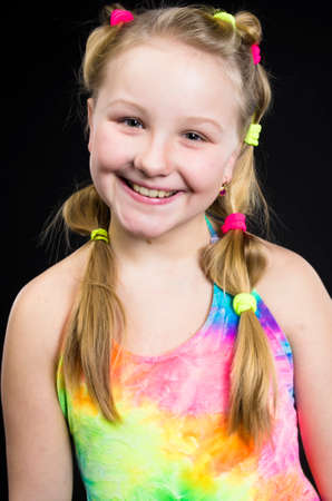 Child girl standing posing in colourful dress in studio black background photo