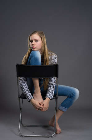 nice teenage girl jeans posing in studio in jeans and shirt on the chair photo