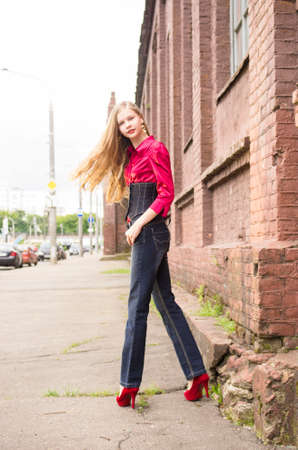 Young female  teen girl in denim and red pose against an old  brick wall. photo