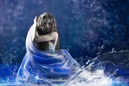 charm temptation: Young girl dance water nereid dance in blue costume in studio. Stock Photo