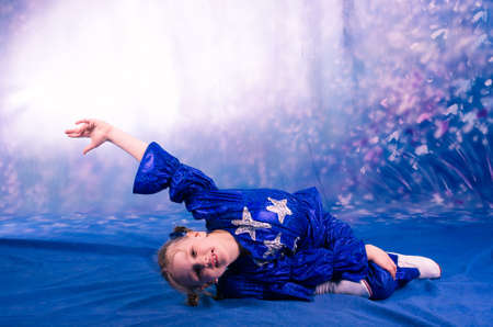 dance preteen: pretty little girl dancing in the blue stared costume in studio Stock Photo