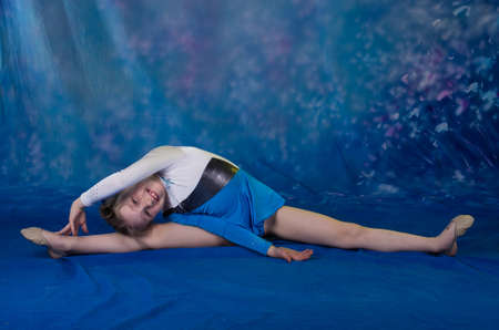 young girl doing gymnastics excercises in studio over blue background
