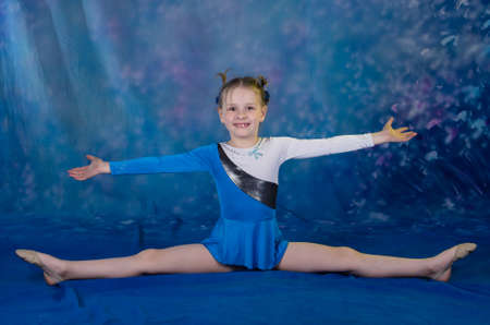 young girl doing gymnastics excercises in studio over blue background photo