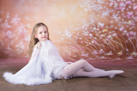 young girl in long white dress with long hair in  the dance pose photo