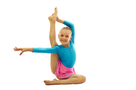 young smiling preteen girl doing gymnastics stretching  exercises on white background isolated