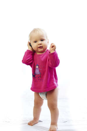 gsm: baby is playing with mobile gsm phone over white background Stock Photo