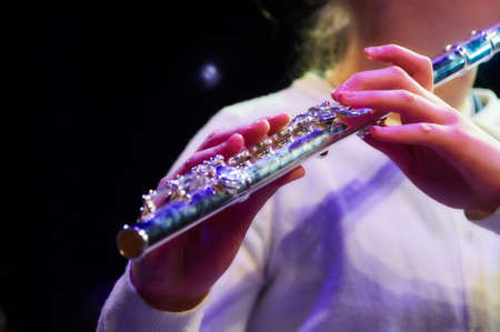 concert flute: girl plaing classical music on flute at the concert in light Stock Photo